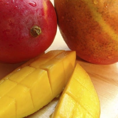 Two whole mangoes and a sliced mango